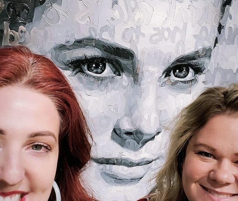 Rochelle and Lea alongside a painting by Christina Major Art